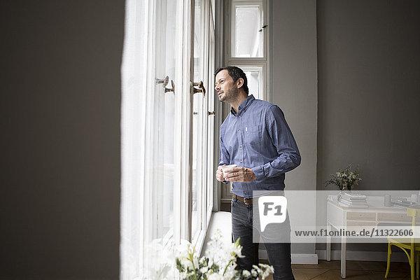 Ein Mann  der durchs Fenster schaut und etwas sieht.