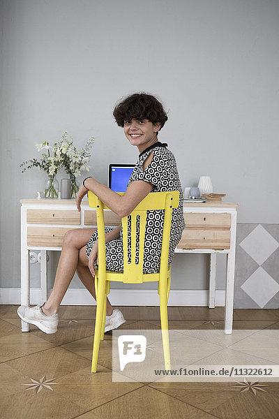 Porträt einer lächelnden jungen Frau  die zu Hause auf einem gelben Stuhl sitzt.