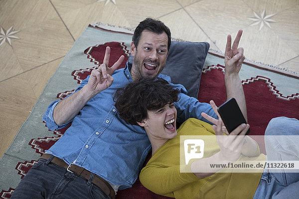 Paar  das zusammen auf dem Teppich liegt und Selfie mit Smartphone nimmt