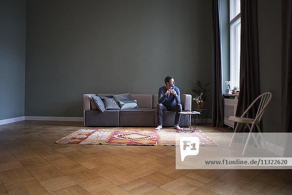 Mann sitzt zu Hause auf der Couch und schaut durchs Fenster.