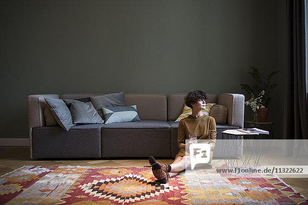 Junge Frau sitzt auf dem Boden in ihrem Wohnzimmer und schaut durchs Fenster.