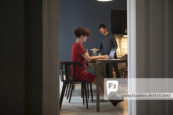 Lächelnde junge Frau mit Laptop in der Küche  während ihr Partner den Tisch deckt.