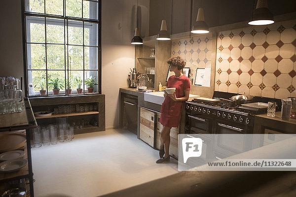 Junge Frau steht in der Küche und schaut durchs Fenster.