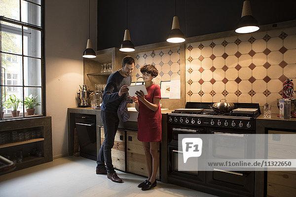 Paar in der Küche mit Blick auf Tablette