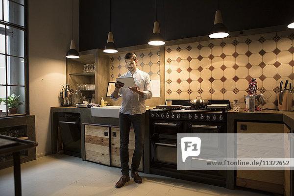 Mann in der Küche stehend mit Tablette