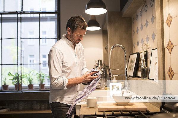 Mann im Küchentrockenglas mit Handtuch