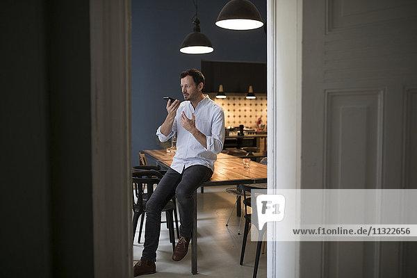 Der Mann am Telefon sitzt auf dem Tisch in seiner Küche.