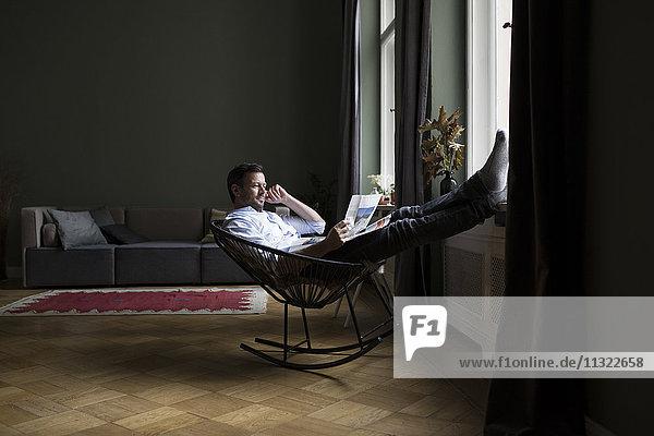 Mann entspannt auf Schaukelstuhl in seinem Wohnzimmer Zeitung lesen