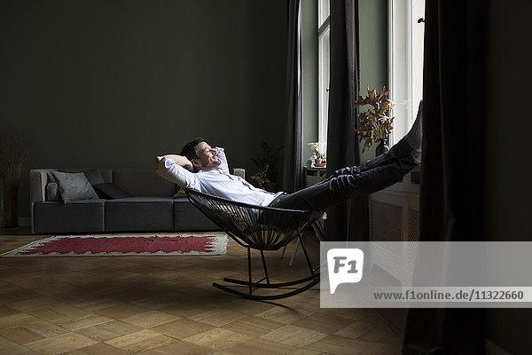 Mann entspannt auf Schaukelstuhl in seinem Wohnzimmer