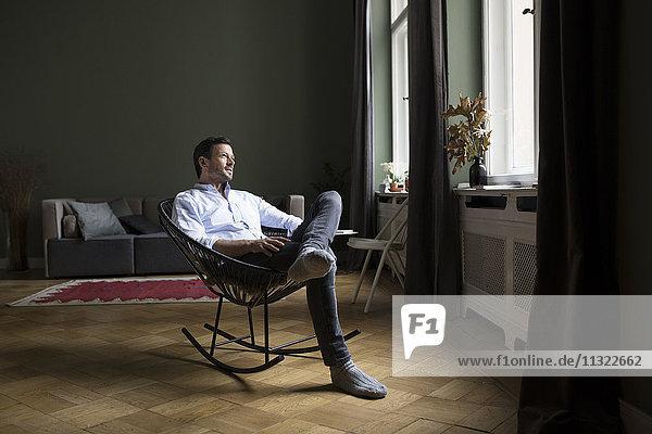 Mann auf Schaukelstuhl im Wohnzimmer mit Blick durchs Fenster