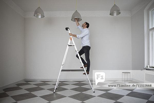 Mann steht auf einer Leiter in einem leeren Raum und wechselt die Glühbirne der Deckenleuchte.