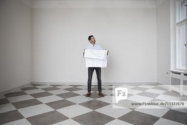 Mann mit Bauplan in einem leeren Raum mit Blick nach oben