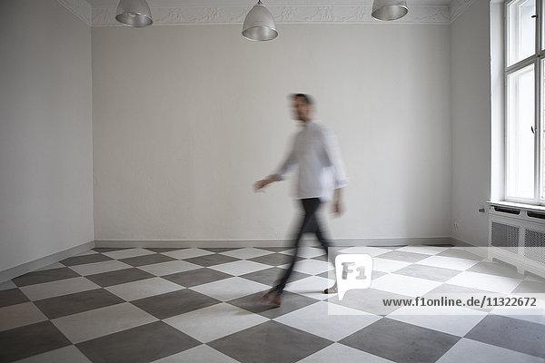 Mann durchquert leeres Zimmer einer Wohnung