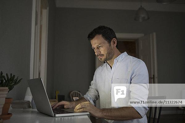 Mann mit Laptop zu Hause