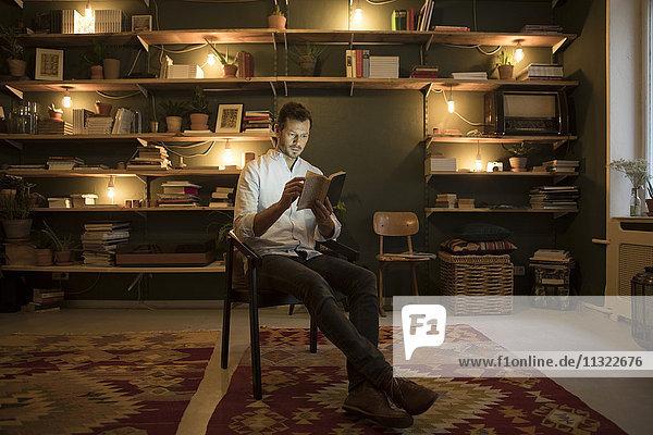 Mann beim Lesen eines Buches zu Hause