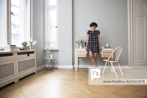 Porträt der glücklichen jungen Frau zu Hause