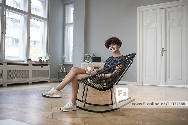 Porträt einer lächelnden jungen Frau  die zu Hause auf einem Schaukelstuhl sitzt.