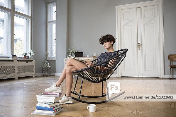 Junge Frau sitzt zu Hause auf einem Schaukelstuhl und liest ein Buch.