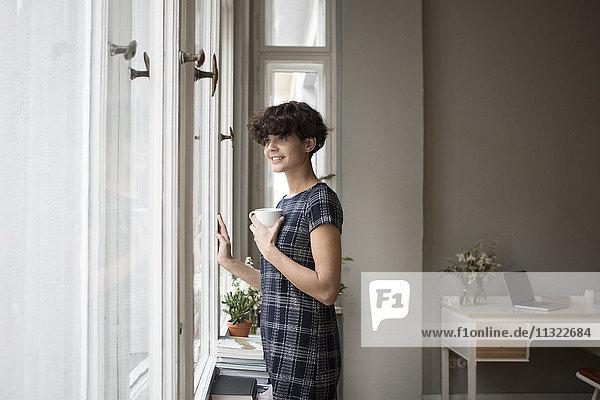 Porträt einer lächelnden jungen Frau  die zu Hause durchs Fenster schaut.