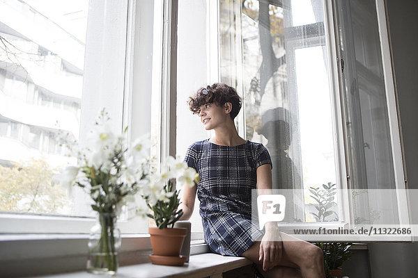 Junge Frau auf der Fensterbank zu Hause sitzend
