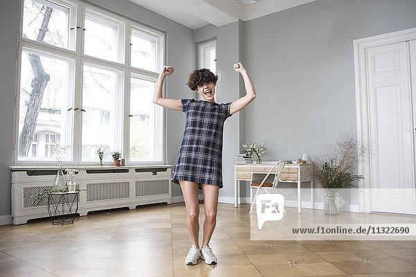 Lustige junge Frau  die zu Hause ihre Muskeln spielen lässt.