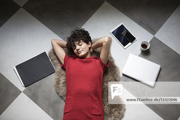 Porträt einer jungen Frau  die sich zu Hause auf dem Boden ausruht.