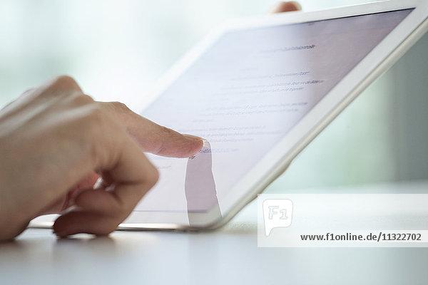 Nahaufnahme der Frauenhände mit Hilfe eines digitalen Tabletts