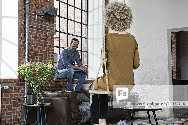 Junge Frau sitzt auf einer Schaukel im Wohnzimmer und redet mit dem Mann.