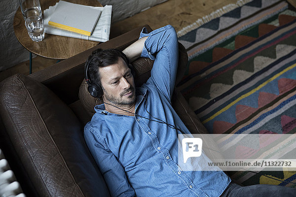 Mann auf der Couch liegend  Kopfhörer tragend Mann auf der Couch liegend, Kopfhörer tragend