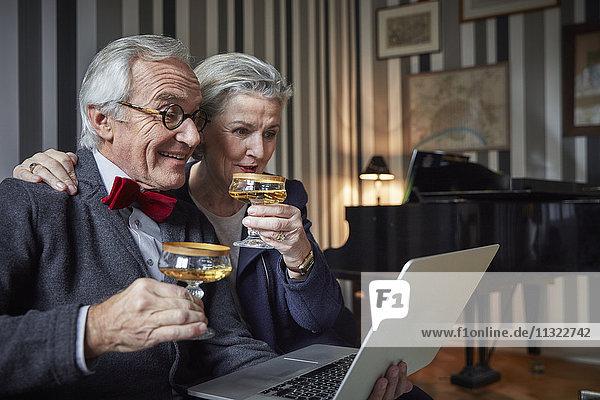 Fröhliches Seniorenpaar trinkt Champagner und benutzt den Laptop zu Hause.