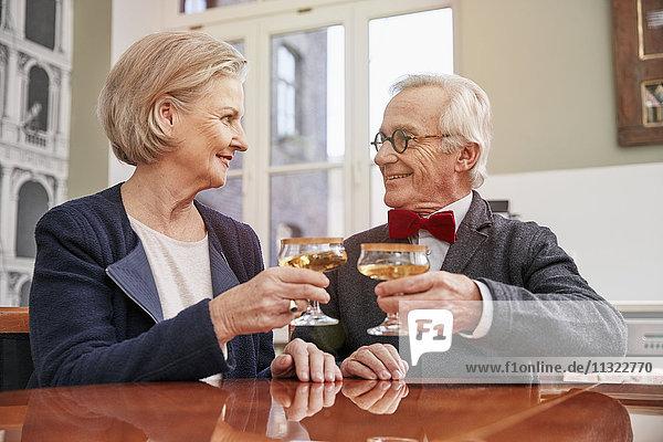 Lächelndes älteres Paar klirrende Champagnergläser