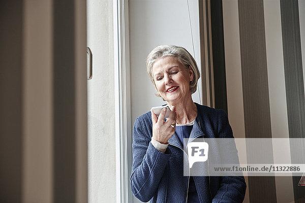 Seniorin mit Handy am Fenster
