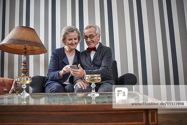 Glückliches Seniorenpaar sitzt auf der Couch mit Smartphone