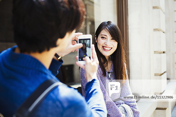 Young Japanese man and woman enjoying a day out in London  standing on a pavement  taking a picture.