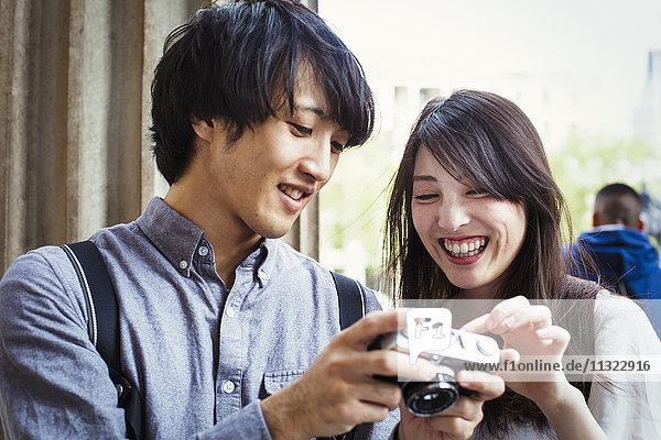 Ein junger Japaner und eine junge Japanerin genießen einen Tag in London  halten eine Digitalkamera in der Hand und lächeln.