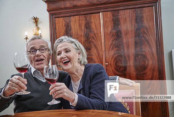 Fröhliches Seniorenpaar singt und trinkt Rotwein