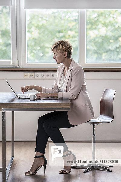 Geschäftsfrau mit Laptop im modernen Konferenzraum
