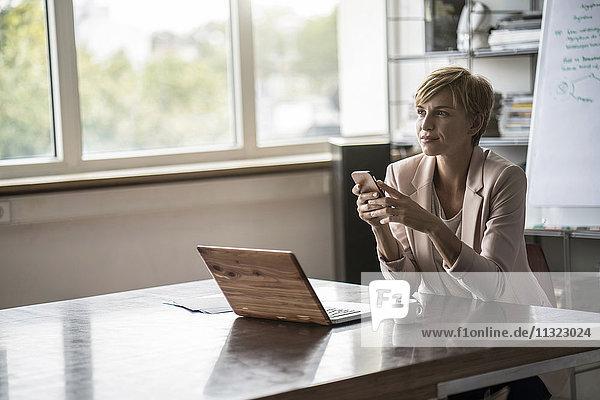 Geschäftsfrau mit Handy und Laptop im modernen Konferenzraum