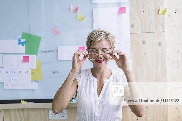 Lächelnde Geschäftsfrau vor dem Whiteboard im modernen Büro