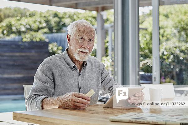 Senior Mann sitzt auf der Terrasse und bezahlt online mit Kreditkarte.