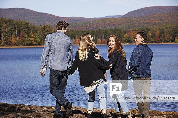 Vier Menschen gehen  Paare Hand in Hand  am Ufer eines Sees entlang.