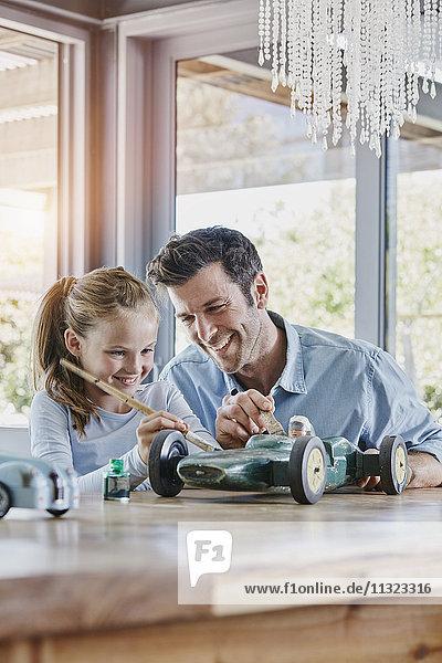 Vater und Tochter malen einen Spielzeug-Rennwagen