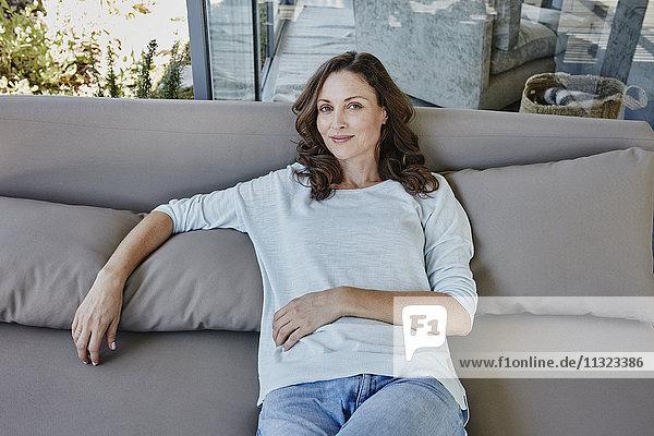 Frau sitzt entspannt auf der Couch auf der Terrasse