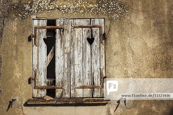 A house with cracked plaster  with broken wooden shutters.