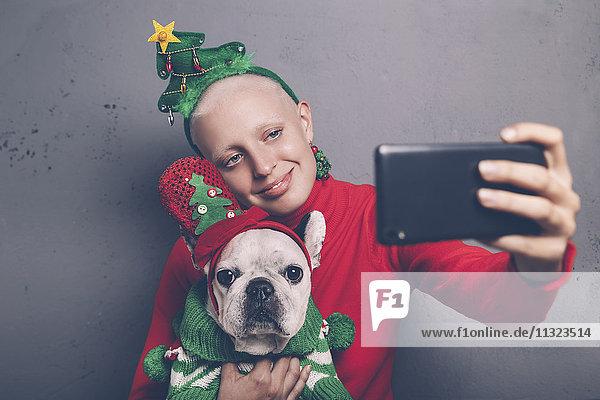 Frau mit französischer Bulldogge nimmt Selfie mit Smartphone in der Weihnachtszeit
