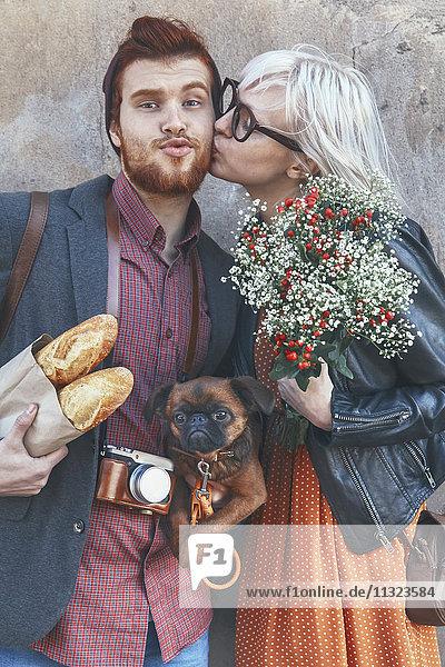 Junges Paar mit Hundekuss im Freien