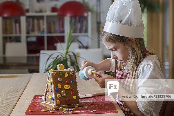 Mädchen Garnierung Lebkuchenhaus