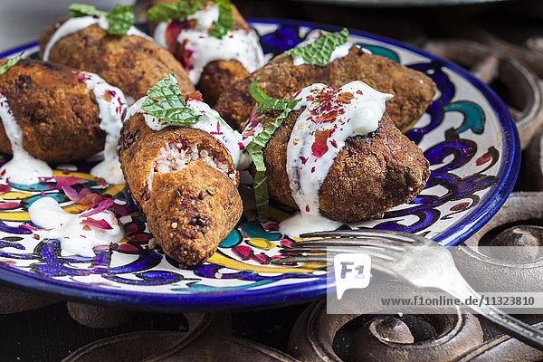Kibbeh  orientalische Fleischkroketten mit Joghurtsauce auf dem Teller