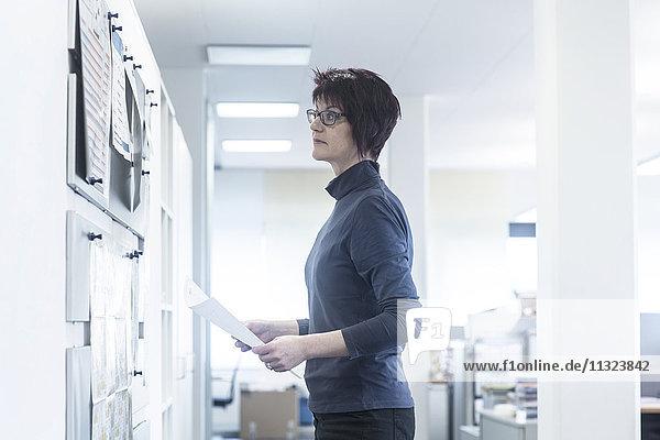 Frau im Büro mit Blick auf das Schwarze Brett