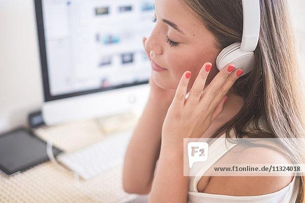 Junge Frau mit geschlossenen Augen Musik hören mit Kopfhörern am Computer